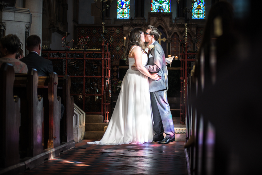 Stain glassed lighting hits Groom during first kiss.