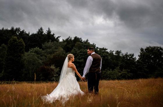 Bride and Groom standing in atmospheric wheatfield